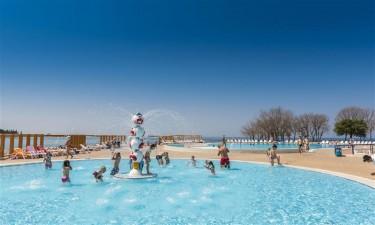 Indbydende poolområde og skøn strand med krystalklart vand